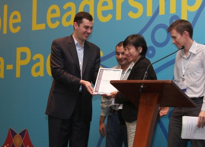 HOME President Bridget Tan receives her award from Asia 21 Fellows John Ciorciari, Soofian Zuberi, and Gregory Fox