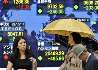 Pedestrians walk past a share prices board in Tokyo on October 2, 2009. Japanese shares fell 246.77 points to close at 9,731.87 at the Tokyo Stock Exchange, hit by heavy losses on Wall Street. (Yoshikazu Tsuno/AFP/Getty Images)