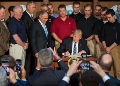 Surrounded by miners from Rosebud Mining, US President Donald Trump (C) signs the Energy Independence Executive Order at the Environmental Protection Agency (EPA) Headquarters in Washington, DC, March 28, 2017. (Jim Watson/AFP/Getty Images)