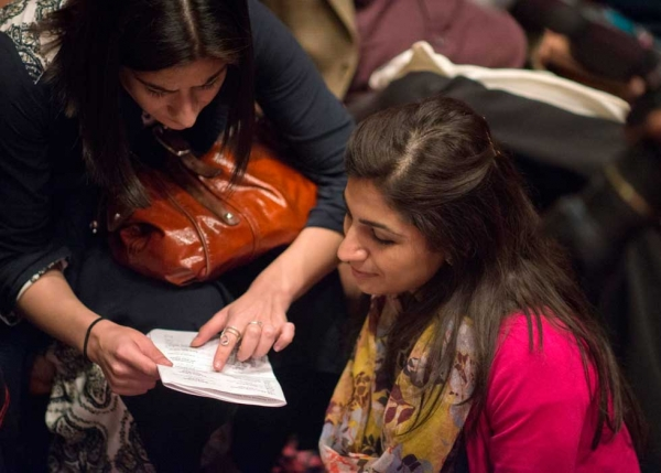 Audience members consulting the LLF program. (Saad Sarfraz Sheikh)