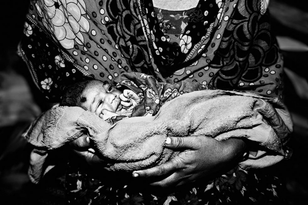 Ria, 12 hours old, is seen in her mother's lap in Dhaka, Bangladesh. (Gazi Nafis Ahmed)