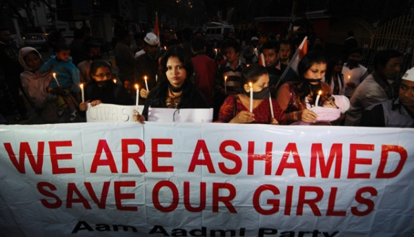 Indian protestors march behind a banner as they take part in a candlelight procession in Guwahati on December 29, 2012, after the death of a gang rape victim from the Indian capital New Delhi. (STRDEL/AFP/Getty Images)