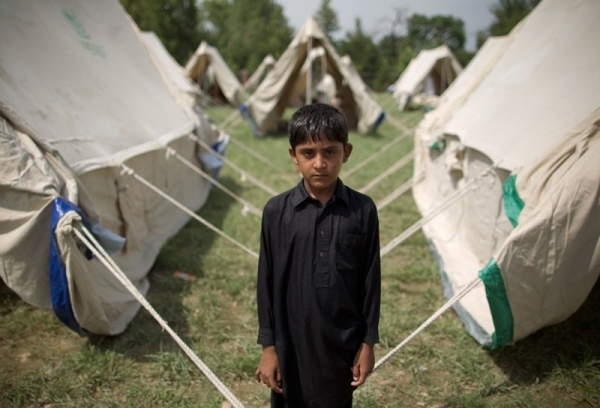 A boy who gave his name as Jeeshan stands outside his tent in a camp set up by the Pakistani army inside a college on the outskirts of Nowshera on August 2, 2010. (Behrouz Mehri/AFP/Getty Images)