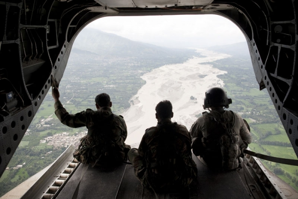 US Army Staff Sargeant Matthew Kingsbury (R) from Bravo Company 2/3 Aviation and Pakistani soldiers sit on the cargo bay ramp of a CH-47 heavy-lift helicopter while looking down at a flooded area while in flight over Swat Valley on August 10, 2010. (Behrouz Mehri/AFP/Getty Images)