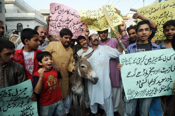 Pakistani cricket fans pose with a donkey as they shout slogans against national cricket team players involved in a match fixing scandal during a protest in Lahore on August 30, 2010. (STR/AFP/Getty Images)