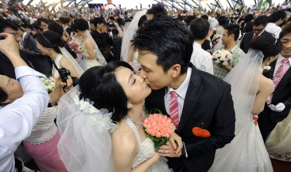 Couples kiss in a Taipei mass wedding