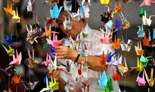 An artist hangs origami before International Day of Peace celebrations at the Quezon City Memorial Circle, east of Manila on September 21, 2010.