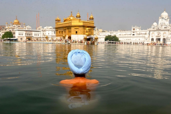 An Indian Sikh devotee takes a dip in the holy sarover (water tank) at the Sikh Shrine Golden Temple in Amritsar on November 5, 2010.