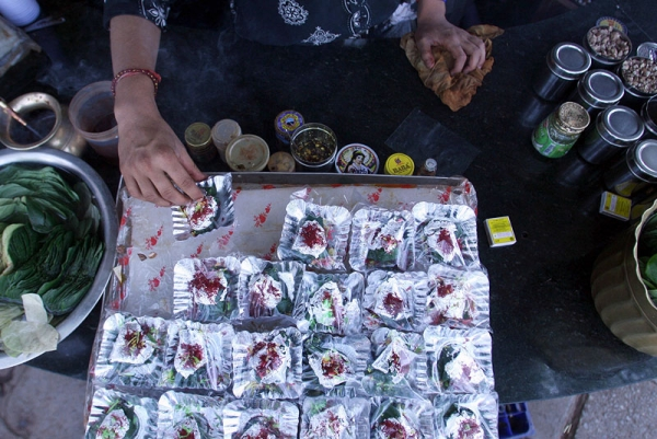 An Indian shopkeeper arranges paan (betel nut products) in silver foils at his roadside shop in New Delhi, India. (Manan Vatsyayana/AFP/Getty Images)