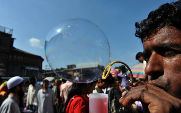A Kashmiri vendor blows bubbles to attract customers ahead of the Eid-ul-Fitr festival at a market in Srinagar on September 9, 2010. (Sajjad Hussain/AFP/Getty Images)