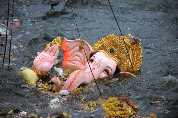 Ganesh is hoisted by a crane into Hussainsagar Lake in Hyderabad on September 22, 2010. (Noah Seelam/AFP/Getty Images)