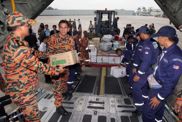 Members of the Special Malaysia Disaster Assitance and Rescue Team (SMART) load emergency and relief supplies into an aircraft for Japan at the Subang Airforce base in Kuala Lumpur on March 15, 2011. (AFP/Getty Images)