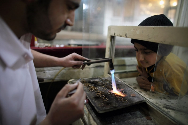A man melts gold to be re-formed as jewelry in a shop in Herat, Afghanistan, on Feb. 27, 2010. Undeveloped gold and other mineral deposits in Afghanistan have the potential to transform its economy. (Majid Saeedi/Getty Images)