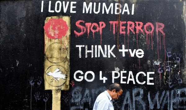 An Indian office worker walks past wall graffiti made after the 2008 terror attacks near the recent blast site at Opera House in Mumbai on July 14, 2011. (Indranil Mukherjee/AFP/Getty Images)