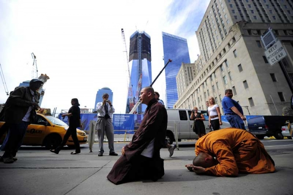 Two Buddhist monks pray in front of Ground Zero and the future One World Trade Center in New York on Sept. 8, 2011. (Emmanuel Dunand/AFP/Getty Images) )