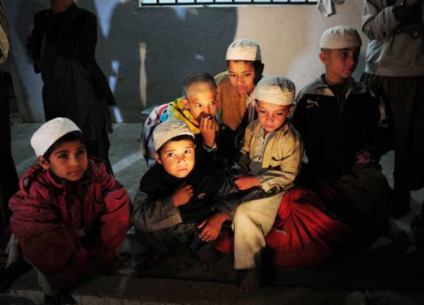 Young Pakistani students sit after being rescued following a police raid on Madrassa Zakarya in Karachi late on December 12, 2011. (ASIF HASSAN/AFP/Getty Images)
