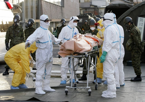 Real-life persons of the year? Rescue workers carry someone believed to be contaminated with radiation to a treatment center in Nihonmatsu city in Japan's Fukushima prefecture on Mar. 13, 2011. (Jiji Press/AFP/Getty Images)