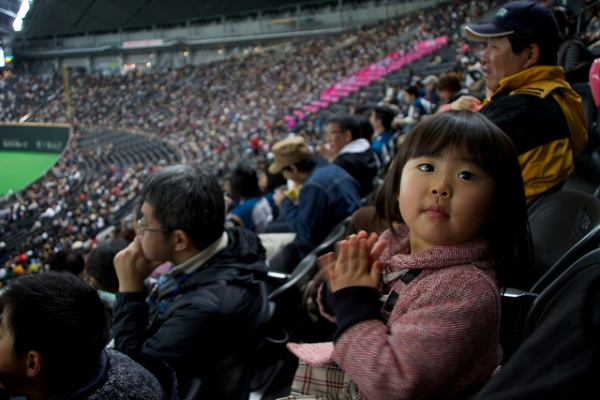 A young baseball fan watches her first game in Sapporo, Japan on April 3, 2012. (MJ/TR (´・ω・)/Flickr)