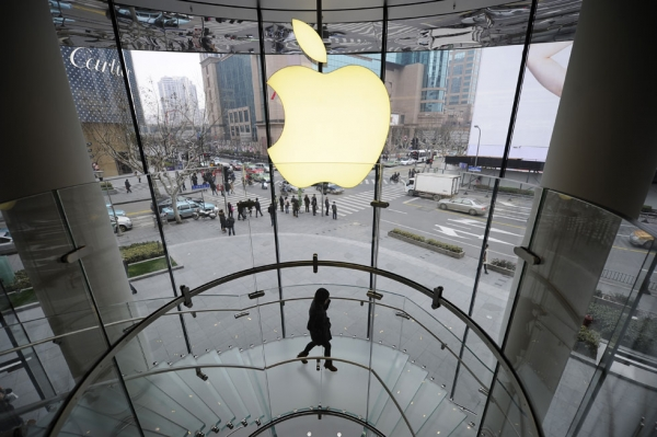 A customer walks under an Apple logo sign at an Apple shop in Shanghai on February 22, 2012. (Peter Parks/AFP/Getty Images)