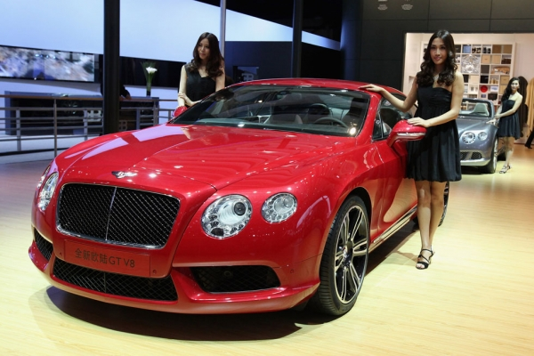 Models stand beside the Bentley Continental GT V8 car during the 2012 Beijing International Automotive Exhibition at China International Exhibition Center on April 25, 2012 in Beijing, China. (Feng Li/Getty Images)