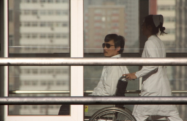 Chinese activist activist Chen Guangcheng (L) is seen in a wheelchair pushed by a nurse at the Chaoyang hospital in Beijing on May 2, 2012. (Jordan Pouille/AFP/GettyImages)