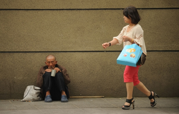 A man begs on a street as a woman passes by in Shanghai on May 9, 2012. China could face an economic crisis in the next 20 years if it does not quickly overhaul its development model, World Bank and Chinese government researchers warned recently. (Peter Parks/AFP/GettyImages)
