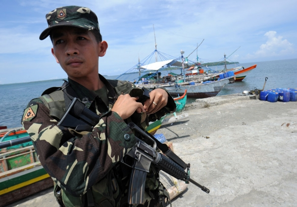 A Philippine soldier stands guard next to fishing boats at a pier in Masinloc town, Zambales province, 140 miles from Scarborough Shoal on May 18, 2012. Philippine President Benigno Aquino told protesters to abort plans to sail May 18, to the disputed South China Sea shoal also claimed by China. (Ted Aljibe/AFP/GettyImages)