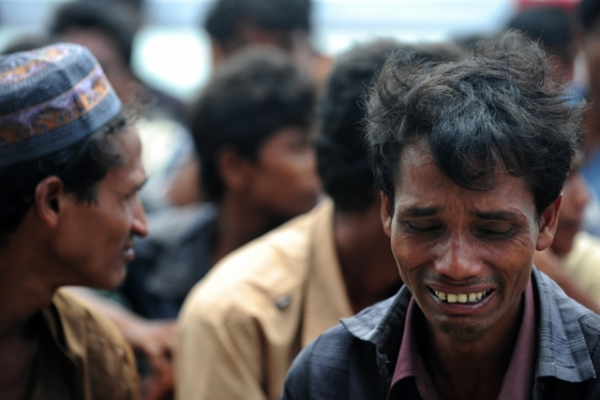 A Rohingya Muslim from Myanmar, who tried to cross the Naf river into Bangladesh to escape sectarian violence, reacts while kept under watch by Bangladeshi security officials after disembarking from an intercepted boat in Teknaf on June 18, 2012. (Munir Uz Zaman/ AFP/GettyImages)