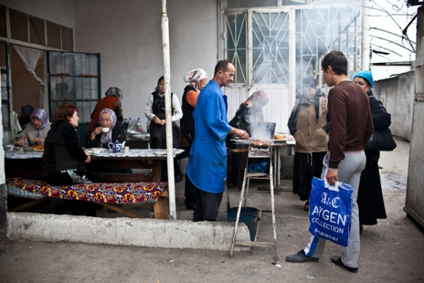 A Kyrgyz cook grills shashlik in a cafe in Osh Bazaar, where customers relax over tea and snacks. (Sue Anne Tay)