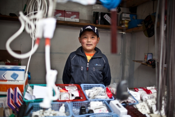 A young Kyrgyz boy mans his father's hardware shop in Osh Bazaar. (Sue Anne Tay)