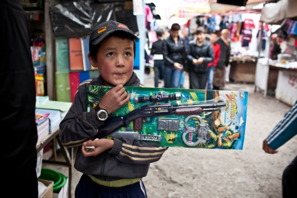 A young Kyrgyz boy clutches his new unopened toy gun in Osh Bazaar. (Sue Anne Tay)