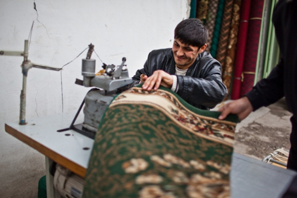 A shop boy helps to measure and trim carpets, mostly produced in China or Turkey, that are sold by the meter. (Sue Anne Tay)