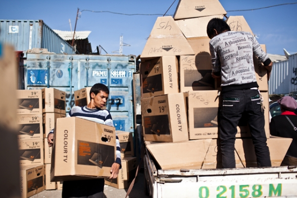 Laborers load up flat-screen televisions from China for distribution into the city. (Sue Anne Tay)