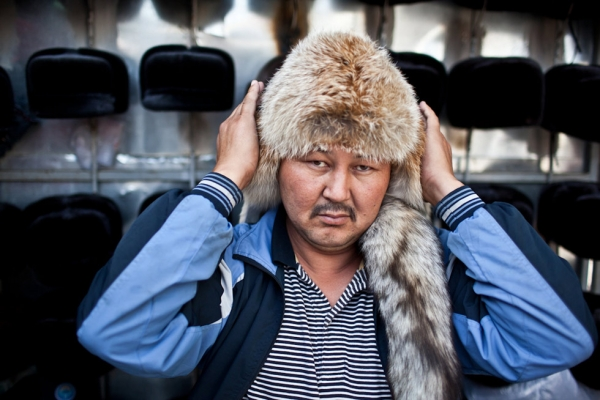 A Kyrgyz fur hat seller adjusts his headgear as he poses for a portrait. (Sue Anne Tay)