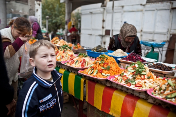 A young ethnic Russian boy stands in front of a wide array of cold salads in the Jalalabad Bazaar. (Sue Anne Tay)
