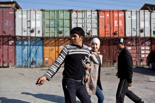 A couple walks by shipping containers that line the parking lot of Dordoi Bazaar, one of the largest in Kyrgyzstan. (Sue Anne Tay)