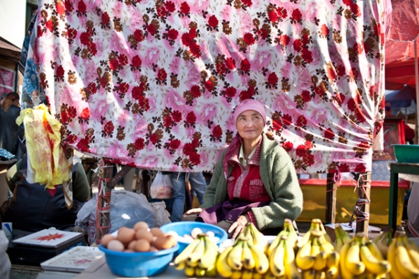 A woman trader sits in front of her fruit stand. (Sue Anne Tay)