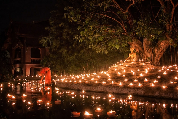 A monk lighting candles in a pond during Visakha Bucha, a day that celebrates Buddha's birth, enlightenment and death, in Chiang Mai, Thailand on June 4, 2012. (CanvasOfLight/Flickr)