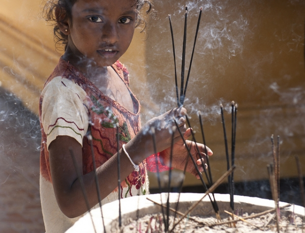 A child at a temple in Sri Lanka holding three sticks of incense in offering (three sticks being traditionally reserved for gods) on May 5, 2012. (Photosightfaces/Flickr)