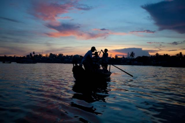 Dawn patrol: vendors heading to market get an early start on the Mekong River in Vietnam. (Hélène Franchineau)