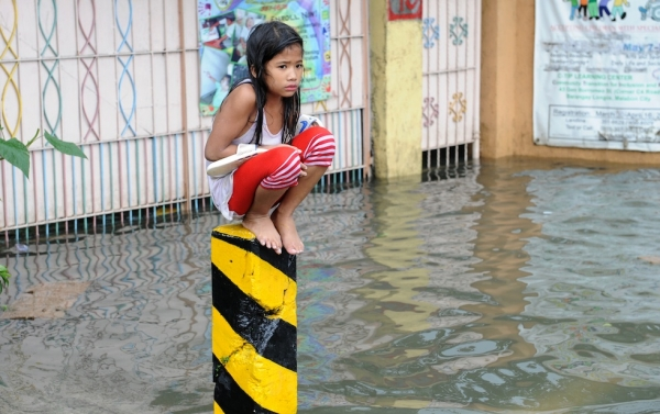 A soaking wet child sits on a post on a flooded street in suburban Manila on August 8, 2012. (Jay Directo/AFP/GettyImages)