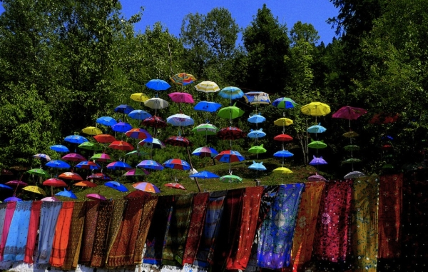 A colorful display of tie dyed scarves and umbrellas by the roadside. (Aamir Choudhry/Flickr)