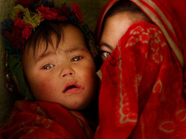 A partially-veiled girl holds a little child close to her side in Afghanistan on June 27, 2012. (james_gordon_losangeles/Flickr)