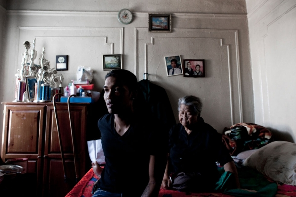 Sovann Ith, 23, sits alongside his grandmother, Somaly Ith, 83, in the living room of their Bronx apartment. (Pete Pin)
