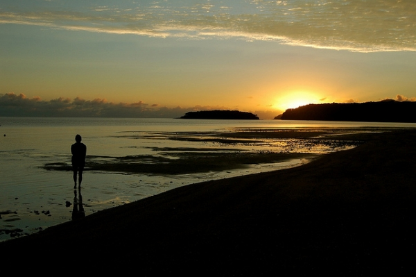 A woman takes in the sunrise off the coast of the Kadavu Island, Fiji on June 29, 2012. (bdearth/Flickr)