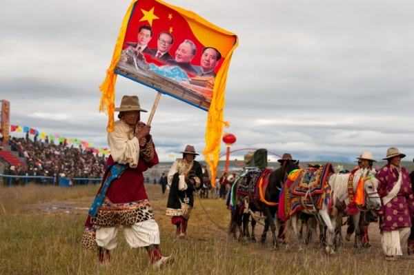 Tibetan cowboy carries a banner which would surely please the government officials in attendance. (Michael Yamashita)