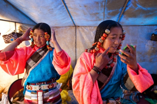Young women in typically colorful Tibetan costumes primp before their upcoming traditional dance performance at the festival. (Michael Yamashita)