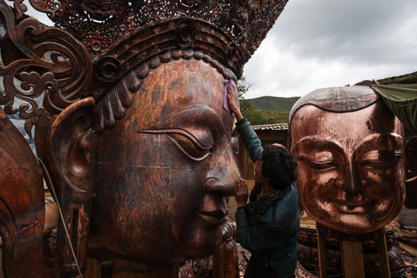 A craftsman polishes the nose of a gigantic copper Buddha at a monastery workshop in Shangri-La. (Michael Yamashita)