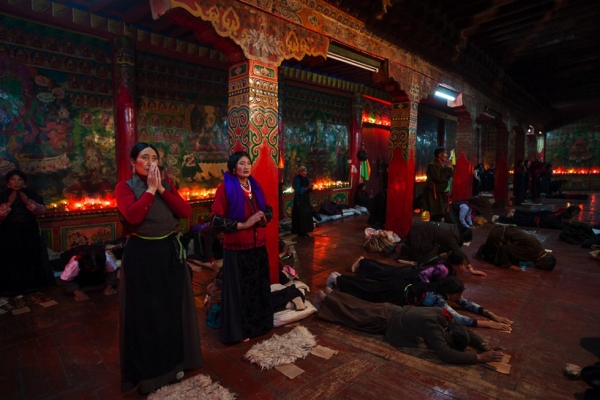 "Locals, who have been invited to Garthar Monastery during a festival, engage in the various stages of the highly ritualized practice of prostration called Chak Tsal, which means ""to sweep clean."" (Michael Yamashita)"