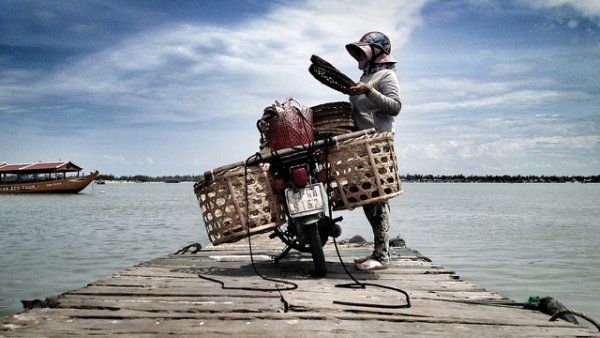 A motorcycle owner parked by the serene waters of Hoi An in Vietnam on September 2, 2012. (Simon Marussi/Flickr)